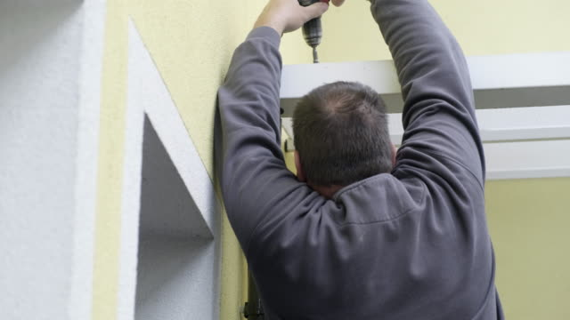 manual worker installing aluminium roof gutter - drill stock videos & royalty-free footage