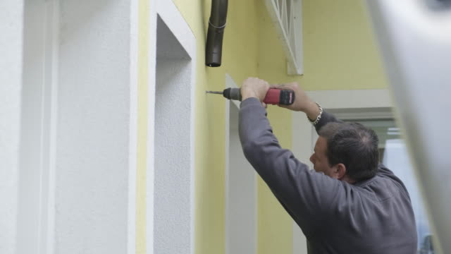 vidéos et rushes de ouvrier manuel installant la gouttière de toit en aluminium - mur