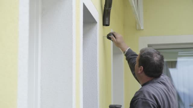 manual worker installing aluminium roof gutter - hammer stock videos & royalty-free footage