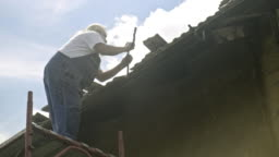 Manual worker installing aluminium roof gutter