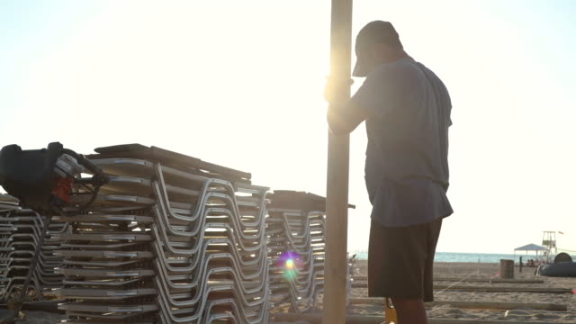 manual worker installing beach umbrella - outdoor chair stock videos & royalty-free footage