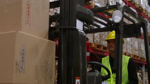 vídeos de stock, filmes e b-roll de trabalhador manual operando empilhadeira carregada com caixas - caixa de papelão