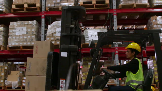 manual worker operating forklift loaded with boxes - loading stock videos & royalty-free footage