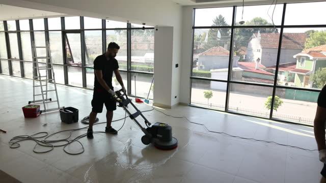 vídeos y material grabado en eventos de stock de máquina depuradora manual de la operación del trabajador mientras trabaja - piso de edificio