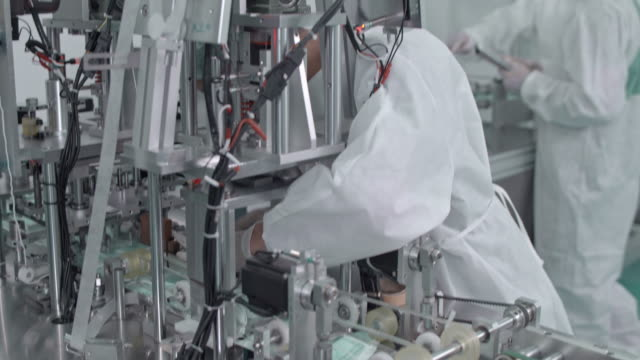 manual worker repairing a machine in protective face mask production line in factory - manufacturing machinery stock videos & royalty-free footage