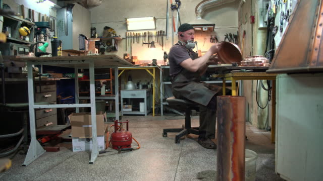 manual worker wearing a protective apron checking the brass details in the workshop - blacksmith stock videos & royalty-free footage