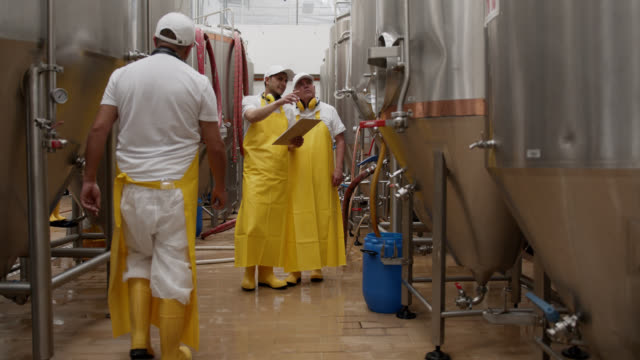 醸造所工場でのタンクの運転を監督する醸造所工場の手動労働者 - 貯蔵タンク点の映像素材/bロール