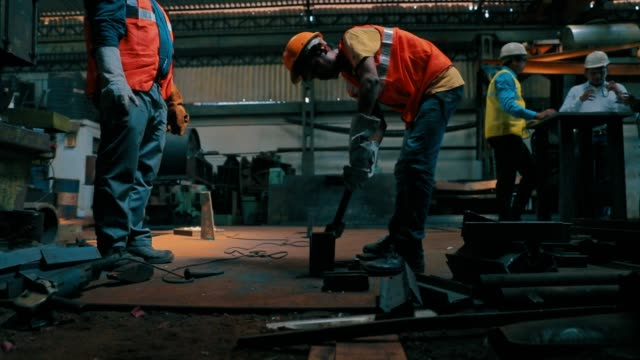 vídeos de stock e filmes b-roll de manual workers on the factory floor - trabalhador da construção civil