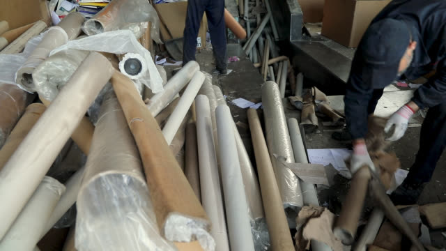 stockvideo's en b-roll-footage met manuele werknemers zetten papieren rollen op transportband. recyclagecentrum. karton recycling - karton