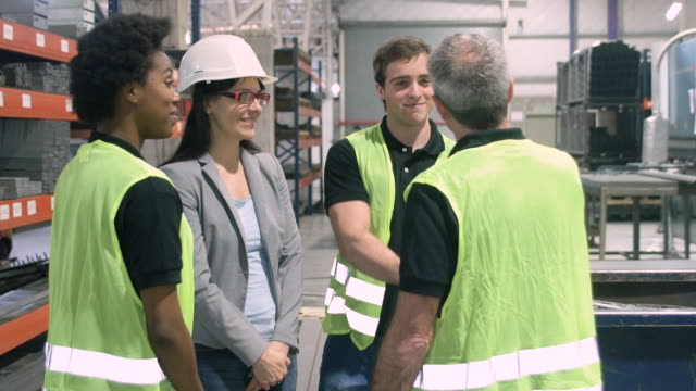 Manual workers shaking hands in factory