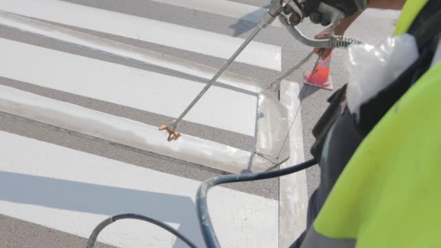 manual workers spray painting crosswalk. professional workers painting zebra crossing on asphalt road - freshly painted stock videos & royalty-free footage