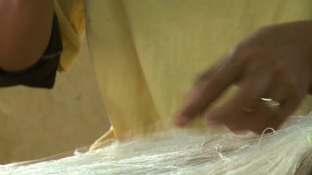 manually removing fibres on silk threads by hand - thread stock videos & royalty-free footage
