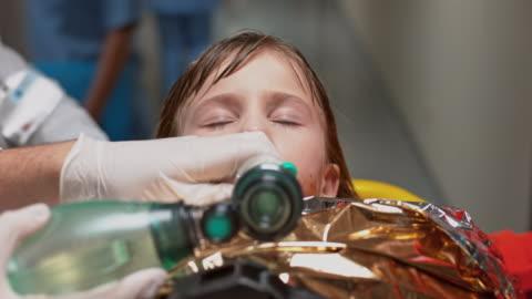 vídeos y material grabado en eventos de stock de manually ventilated hypothermic child being brought to emergency - primeros auxilios