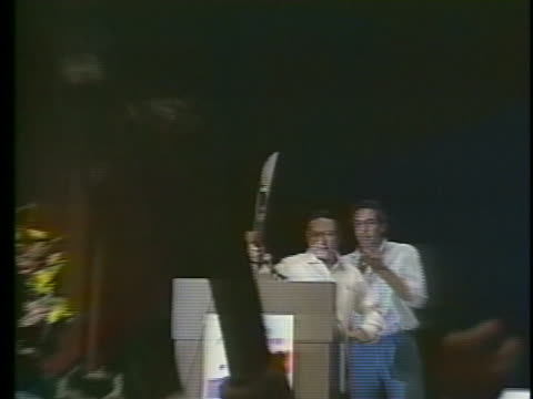 manuel noriega waves a machete above his head during a speech to a cheering audience in panama city in 1988 - crime or recreational drug or prison or legal trial stock-videos und b-roll-filmmaterial