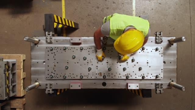 stockvideo's en b-roll-footage met manuel worker in een productielijn van een deel van de machine - arbeidsveiligheid