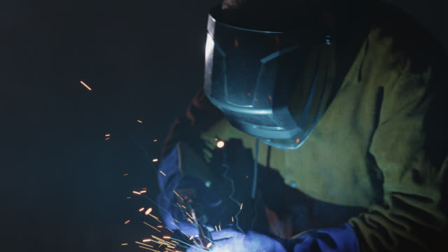 slo mo cu manufacturing professional uses welding torch on metal in warehouse - metal industry stock videos & royalty-free footage