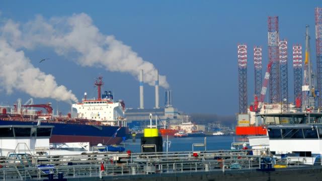 vídeos y material grabado en eventos de stock de muchas actividades en el puerto de rotterdam con grúas y plataformas petrolíferas - rotterdam