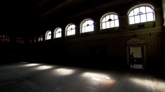 Many arched windows brighten a dim hall in the High Royds former psychiatric hospital, Yorkshire. Available in HD.