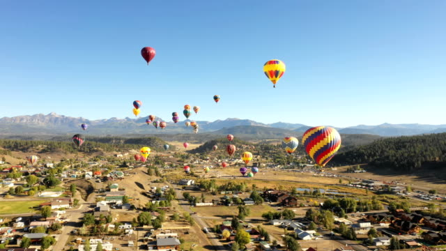 many beautiful balloons rising out of small colorado town - hot air balloon stock videos & royalty-free footage