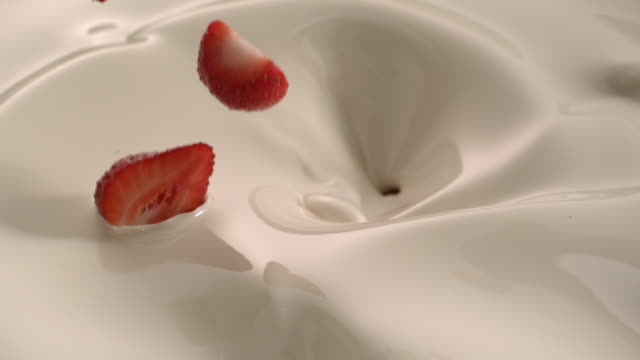 many beautiful strawberries falling down in white cream create swirl and splashes in slow motion tabletop - food styling stock videos & royalty-free footage