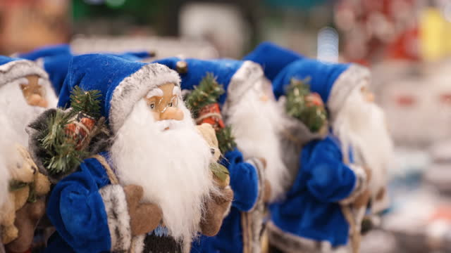 many blue santa claus xmas decoration figures in shop - weihnachtsmütze stock-videos und b-roll-filmmaterial