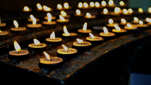 vídeos y material grabado en eventos de stock de muchas velas ardientes con poca profundidad en la iglesia - luto