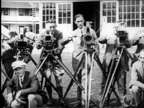 vídeos de stock e filmes b-roll de b/w 1925 pan many cameramen cranking cameras outdoors for camera / documentary - camera fotografica