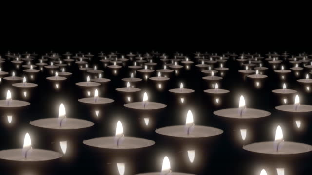 many candles floating on water surface burn in dark. - memorial event stock videos & royalty-free footage