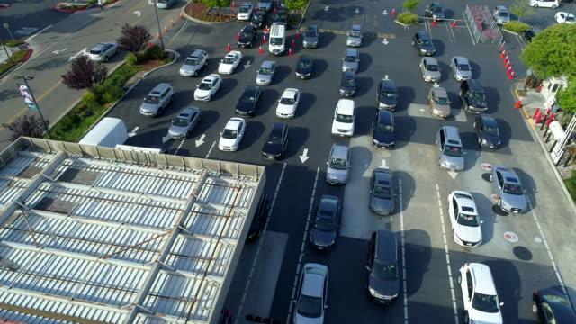 vidéos et rushes de beaucoup de voitures attendent dans la ligne à la station d'essence. vue aérienne. - tous types de crises