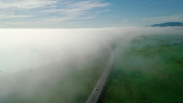 many cars driving cabrillo highway under the fast moving low cloud coming from the pacific ocean around the hills in san simeon, california, nearby arroyo del oso.  the windy sunny spring day. aerial drone video with the slow panning camera motion. - fog stock videos & royalty-free footage