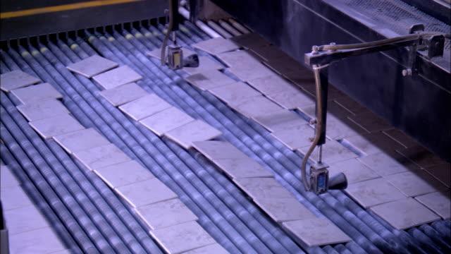 vidéos et rushes de many ceramic tiles move across a wide conveyor in a factory. - céramique