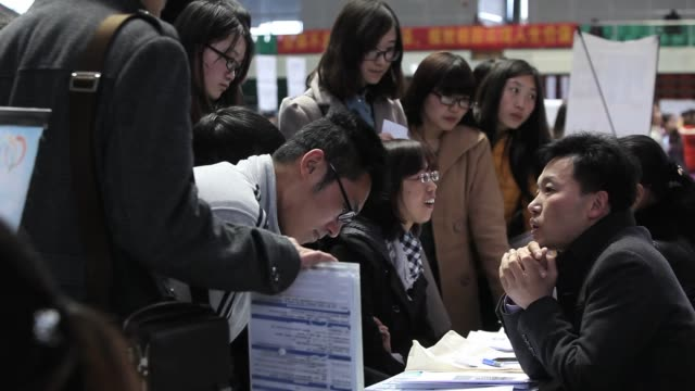 Many Chinese graduating students listen to job description as they look for jobs at a special job fair helping 2013 college graduates to look for...