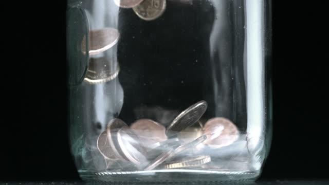 many coins pouring into glass jar close up - savings stock videos and b-roll footage