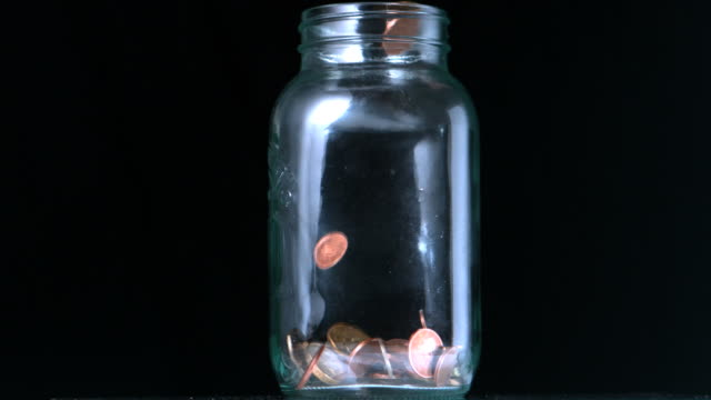 Many coins pouring into glass jar