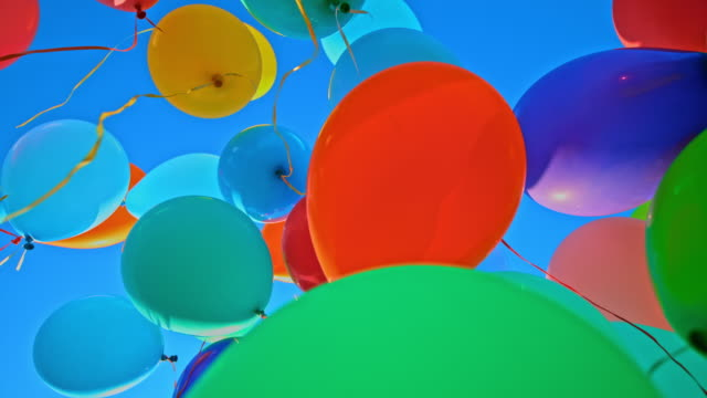 slo mo ld many colourful balloons released into the blue sky - flying stock videos & royalty-free footage