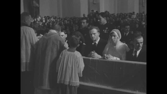 VS many couples kneeling at altar and in pews getting married in crowded church priest and other clergy administer to them women's hair is covered /...