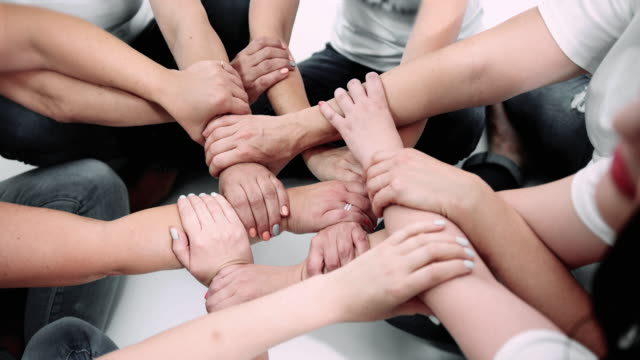 many female hands are joined together in unity - hands clasped stock videos & royalty-free footage