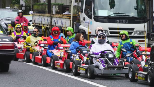 many foreign visitors enjoy riding the go-kart tokyo kart tour on the road around shibakoen minato ward tokyo japan on jan. 19 2018. - minato ward stock videos & royalty-free footage