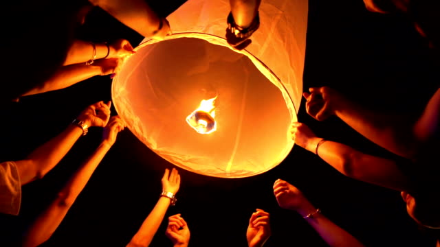 vídeos de stock e filmes b-roll de slo mo many hands floating sky lantern loi krathong and yi peng traditional festival, chiang mai province, thailand - lanterna de papel
