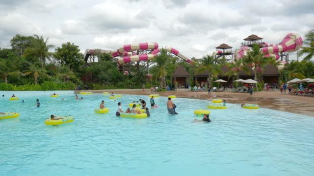 vídeos de stock e filmes b-roll de many happy people playing in pool water in aqua park on a beautiful summer day on their holidays - escorrega de água