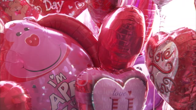 Many heart-shaped helium balloons float in the air.