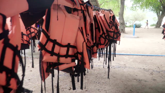 many Life vests on clothes line are only orange color.