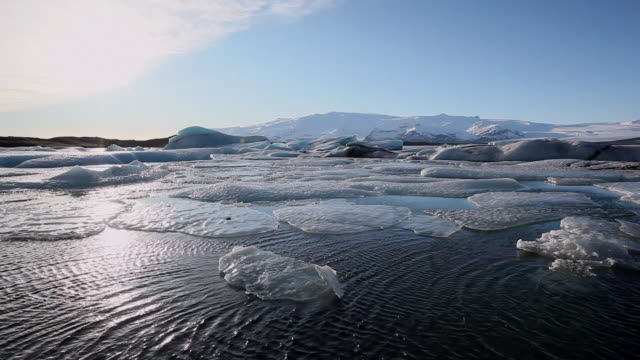 ws many melting glaciers floating in jokulsarlon lake at sunset / iceland - jokulsarlon stock-videos und b-roll-filmmaterial