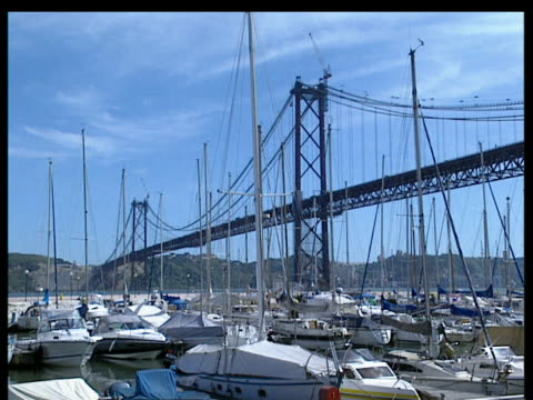 many moored yachts in harbour of marina in foreground - 4月25日橋点の映像素材/bロール