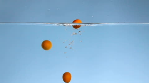 many orange kumquats fall under water slow motion video - small group of objects stock videos & royalty-free footage