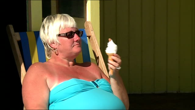 many parts of the country experience autumn heatwave; england: ext / sunny woman sunbather in deckchair eating ice cream - deck chair stock videos & royalty-free footage