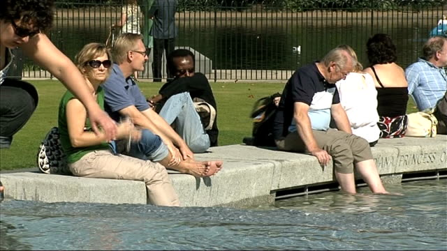 many parts of the country experience autumn heatwave england london hyde park ext two people sunbathing on grass in october heatwave / general view... - the serpentine london stock videos & royalty-free footage