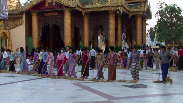 Many people cleaning floor with brooms