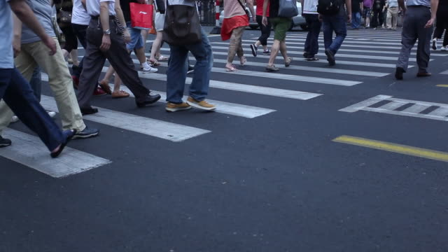 Many people crossing at a pedestrian crossing