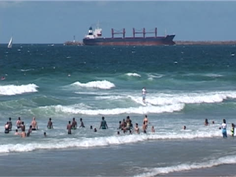 vídeos y material grabado en eventos de stock de many people in waves, tanker behind, mws - elmina